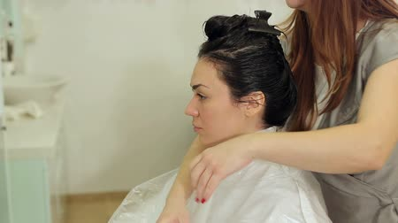 prádelník : Hairdresser puts a protective cape on the shoulders of the girl and straightens the paper collar before cutting. The process of working in the barbershop.