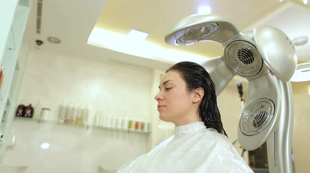 toalha : A young girl dries her hair in a hairdresser with a professional hair dryer. Portrait of a young woman in a Barber shop.