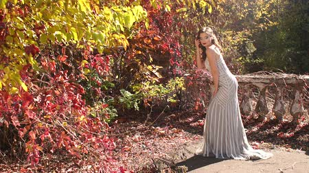 október : A charming girl in an evening dress posing for the camera in a beautiful autumn Park on the background of wild grapes with red leaves.