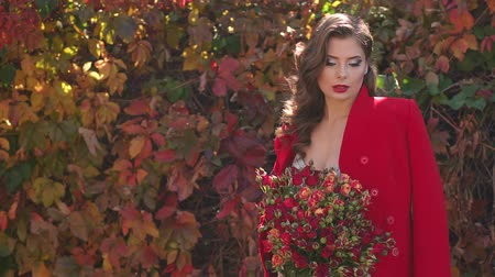 október : Portrait of a gorgeous girl in a dress and a red coat and with a bouquet of autumn flowers in an autumn Park on a background of red and yellow leaves.