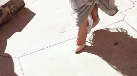 high heel shoe : Close-up of a girl in an evening dress and in high heels walking along the road, the dress stretches across the floor. Close-up of the legs of a girl in high-heeled shoes.