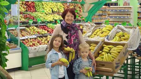 представитель старшего поколения : Happy old woman with small children in the supermarket. Grandmother and grandchildren buy bananas in the store. Slow motion.