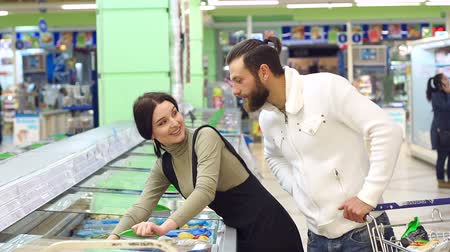 troli : Cute caucasian couple choose frozen foods from the supermarket refrigerator. A young married couple buy frozen berries in a supermarket standing near a large refrigerator. Slow motion. Stock mozgókép