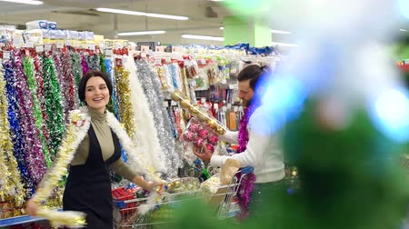korale : Happy loving couple buying Christmas decorations and gifts for Christmas. The couple is having fun at the Christmas holidays in the supermarket. Slow motion. Wideo