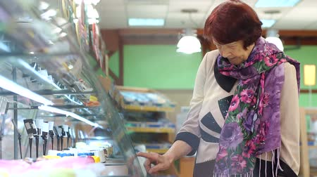 продуктовый : Elderly pretty woman shopping for fresh healthy food in the supermarket. Positive elderly woman consumer with bakery products in the food shop.