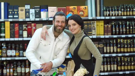 kifejező pozitivitás : Portrait of a young fashion couple in a supermarket or in a wine shop with a full cart of products. Bearded man with his wife in a liquor store, portrait. Slow motion. Choosing wine for dinner.