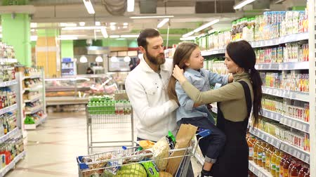 corredor : Portrait of happy family with cute little girl choosing juice in grocery store, confectionery. Beautiful parents and their daughter are choosing sweets in supermarket. Slow motion.