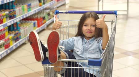 kciuk : A little happy girl sits in a grocery cart in a supermarket and shows her thumb up. Portrait of a cute girl having fun in the supermarket.