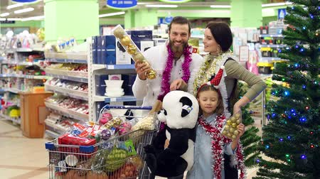 部門 : Portrait of a happy family in the supermarket before christmas. A happy family with a child buys groceries, Christmas decorations, and presents for Christmas or New Year in a large supermarket. 動画素材