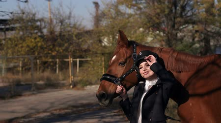 lóháton : Portrait of beautiful girl in special clothes and hat with brown horse in autumn. Young woman with her horse. Young professional model girl posing with horses and with a horse. Stock mozgókép