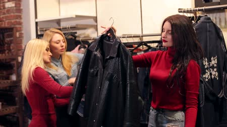 butik : Three cheerful happy girlfriends are looking at clothes in a modern store. Funny teen girls buy jackets in a clothing store. Portrait of three beautiful young women shopping in a clothes shop.