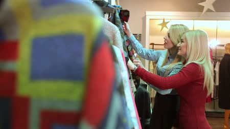 megpróbál : Two fashionable blonde girls choose clothes in a large clothing store. Slender young women buy fashionable clothes in a modern shopping center.