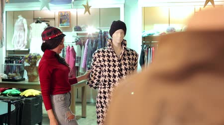 pansuman : A young girl in jeans and a red sweater buys clothes in a clothing store, she looks at the coat that hangs on a mannequin. Stok Video