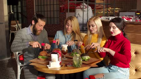 juntar : A group of cheerful carefree young people in the restaurant, they take the equipment in their hands and get ready to eat tasty burgers. A group of hipsters eating beautiful burgers from black bread.