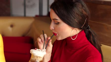 elegant dessert : Close-up portrait of a young sexy girl in a cafe, she drinks a cocktail with Cola and whipped cream. A girl with red lipstick drinks a cocktail from a straw sitting in a cafe with a girlfriend.Slow mo Stock Footage