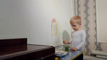 поясница : Little boy paints with a brush on the wall at home. Funny boy draws with colorful paints on a white wall.