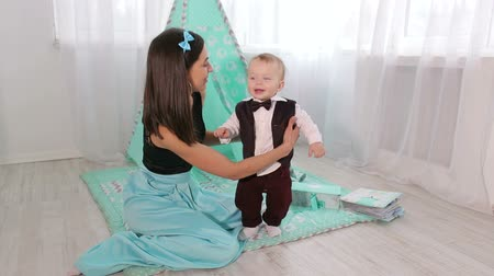 o : Cute happy little boy playing with his mother in the nursery, he is wearing a tuxedo with a bow tie. The first steps of the little boy at home, the mother holds her baby. Stok Video