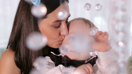żyrandol : Gentle happy mother kisses and hugs her little one-year-old son who is played in transparent stones. Portrait of a happy mother with a young son. Happy family. Wideo