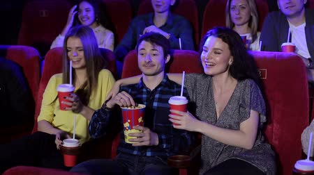 kola : Group of friends watching a movie in a movie theater, eating popcorn and drinking coke. Two girls flirt with one guy in a movie theater, they fool around and have fun. Friends throw popcorn at cinema. Stok Video