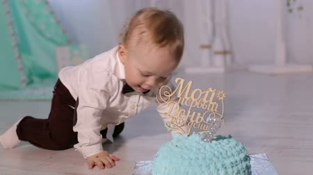 príncipe : Close-up of a little boy playing with the first birthday cake, he gets his hands dirty in cream. A cute one-year-old boy in a white shirt and bow tie is playing with a blue birthday cake.