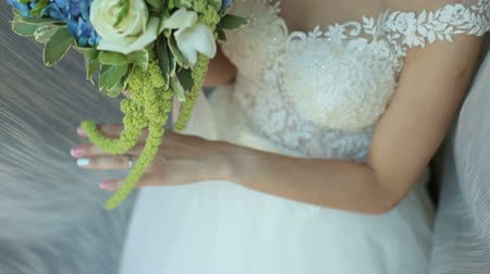 подвенечное платье : Close-up of the bride holding her wedding bouquet, she gently touches the flowers.