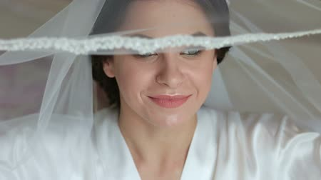 элегантность : Gorgeous bride portrait with make-up in the morning in room near window. Beautiful woman getting ready for wedding day, holding veil and smiling. Face close-up. Sensual moment.