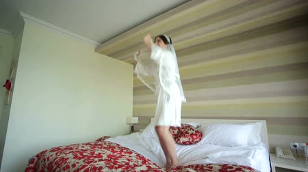negligee : Happy young bride in a negligee jumping on the bed. Wedding day. Portrait of a happy bride. Stock Footage