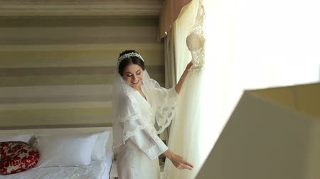 sentiment : Bride in silk dressing gown holding and admiring her beautiful wedding dress in front of the window. Wedding morning, brides preparations. Gorgeous bride in luxury dress is getting ready for wedding.