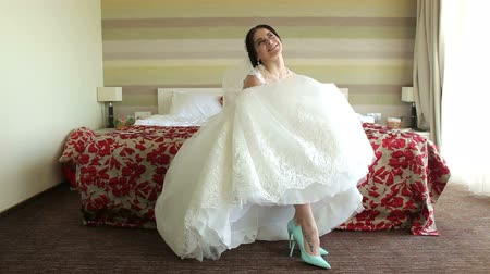 серьги : Happy bride sitting on the bed in the hotel shows her beautiful shoes and straightens her skirt on the dress.