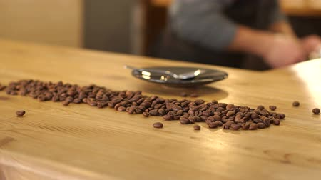 ileri : Close-up of coffee beans on a wooden table in a coffee shop, standing next to a plate with a spoon. In the background, the image of a male Barista who prepares coffee.