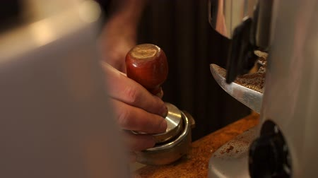 portafilter : Barista makes espresso in cafe. Barista press coffee with tamper in portafilter. Brewing coffee equipment. Barista brew espresso drink in cafe. Coffee making in coffeehouse. Stock Footage