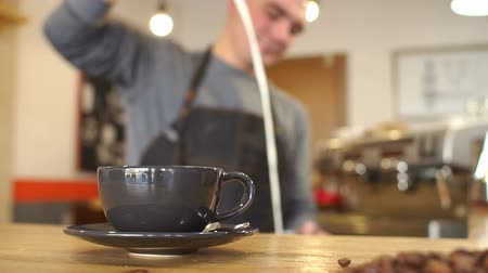 étkező : A blurry image of a man who makes a fragrant latte in a coffee shop, he pours milk into a Cup. In the foreground is a black Cup of coffee. Stock mozgókép