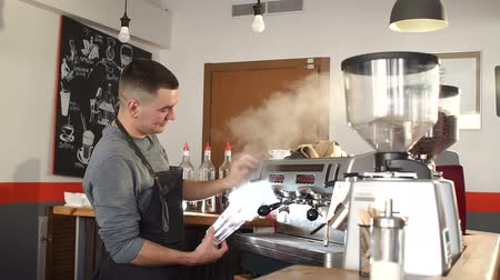 kávézó : Portrait of a young man working in a coffee shop with modern equipment. Barista prepares hot fragrant cappuccino. Coffee machine in steam, barista preparing coffee at cafe.
