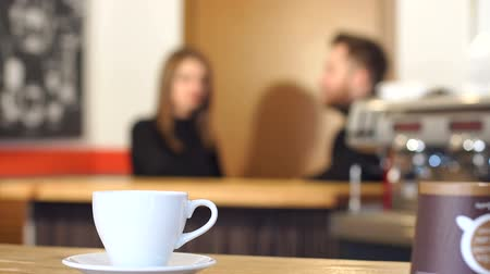 çay kaşığı : The cup of coffee on the background of the couple in the cofee shop. Close-up image of a white cup on a table in a coffee shop, in the background are a couple in love at the bar counter. Stok Video