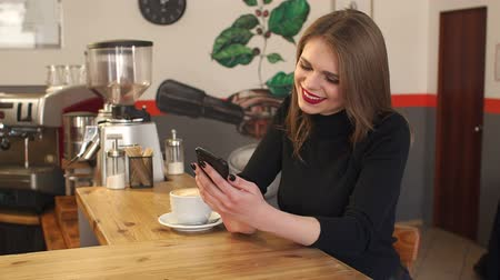 düzen : Beautiful sexy girl sitting at the bar in a coffee shop with a Cup of coffee and a phone. Portrait of a young girl in a cafe with a latte and a phone in his hands. Slow motion.