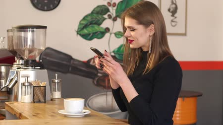 kávézó : Young stylish girl blogger takes pictures of a Cup of cappuccino in a cafe sitting at the bar. A beautiful teen girl takes a selfie in a cafe with a Cup of coffee. Slow motion.