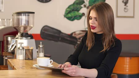 ruj : A beautiful girl in a black sweater with red lipstick sits in a fashionable coffee shop with a small tablet, she drinks a fragrant cappuccino and looks at the screen of her gadget. Slow motion.