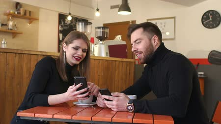 по электронной почте : A young cheerful couple rest in a coffee shop and look at the phone screens. A couple of fashionable people are sitting in a coffee shop with phones, a Barista is preparing coffee in the background.