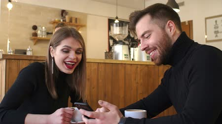 kávézó : Close-up of happy cheerful teenagers sitting in a cafe at a table looking at the phone screen and laughing pointing a finger at the screen. Slow motion. Couple in coffee shop connected with smartphone
