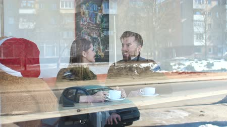szórakozási : View through the window of a young couple in a coffee shop. Loving couple resting in a small cozy coffee shop in the winter, they drink cappuccino sitting at a table near a large window.
