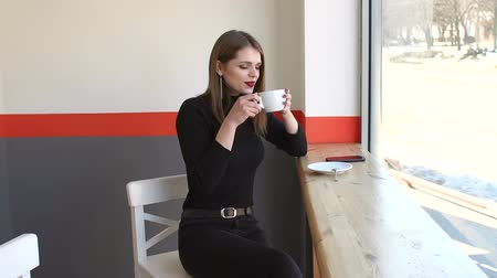 pult : Beautiful cute girl in the cafe near the window, she drinks coffee and smiles. Young woman sitting by the window at the bar counter in coffee shop. Teen girl hold cup of coffee in hand look in window.