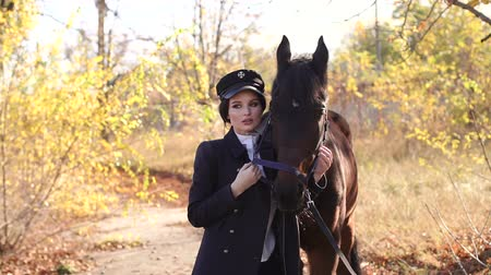 ecuestre : Portrait of beautiful girl in special clothes and hat with brown horse in autumn. Young woman with her horse. Young professional model girl posing with horses and with a horse. Archivo de Video