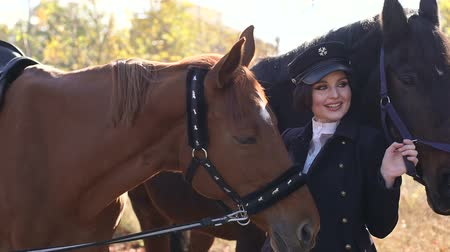 égua : Professional model poses with two horses against the background of the autumn forest, she is dressed in riders clothes. Close-up. Slow motion. Vídeos