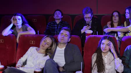 arquibancadas : Young people watching a boring movie at the cinema, all doing different things, sleeping, eating popcorn, taking selfies, yawning. Loving couple sleeping in chairs.Bored people fall asleep in a cinema Vídeos