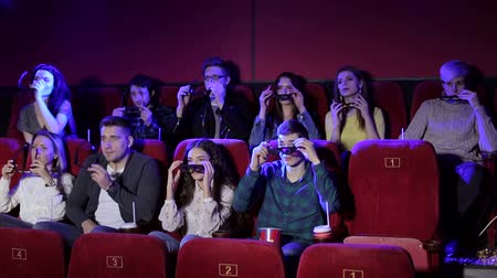 cinematography : A group of young people and teenagers puts on a glasses to watch a 3D movie in a movie theater. Young friends watching a 3d film at the cinema. Group of friends watching 3D film and eating popcorn. Stock Footage