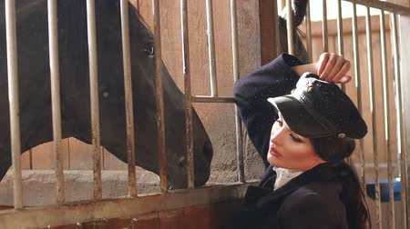 Çingene : Young seductive girl with professional make-up in the village stable near the brown horse. Model posing in the stable on a horse farm. Slow motion.