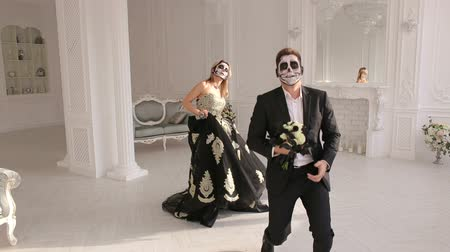 фольклор : Young active people in costumes and makeup for Halloween, they dance in a bright white room with a vintage interior. Couple of zombies. Halloween face art.