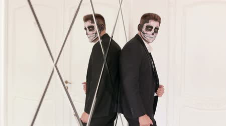 mascarar : Portrait of man in suit with Halloween skull make-up, he stands leaning on the mirror wall. Devil makeup on face for halloween party. Death- painted male face. Businessman with make-up skeleton.