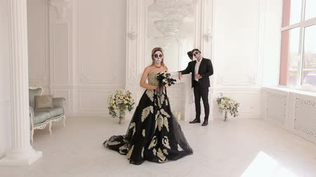 фольклор : A man and a woman in a dress and costume with a creepy Halloween makeup, they stand in a beautiful white vintage room of an ancient castle. Couple of zombies. Halloween face art.