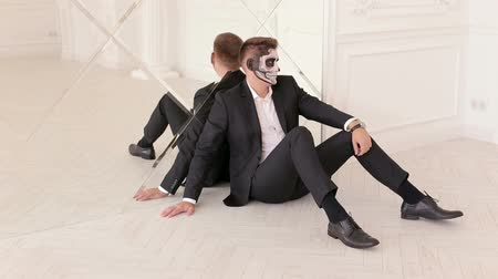 готический : Close-up portrait of a man with a skull makeup dressed in a suit sitting on the floor leaning against the mirrored wall. Dia de los muertos. Day of The Dead. Halloween. Стоковые видеозаписи